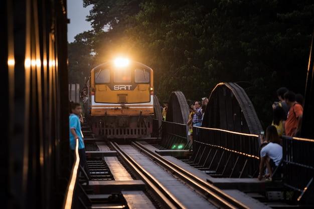 Os turistas vêem o trem na ponte do rio kwai em kanchanaburi.