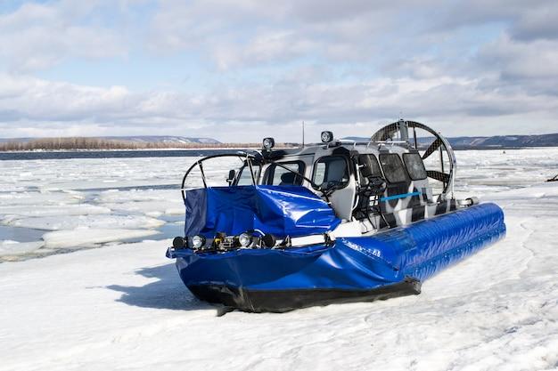 Os turistas viajam no gelo de um rio congelado em barcos em almofadas de ar.