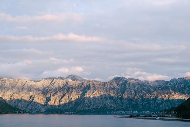 Os últimos raios de sol no topo das montanhas rochosas sobre a cidade de dobrota em