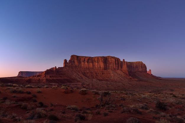 Os últimos raios do sol poente iluminam a icônica vista de monument valley, na fronteira entre o arizona e utah, eua