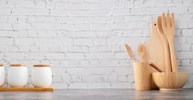 Os utensílios de cozinha e os copos de madeira na parede de tijolo branca texture o fundo.