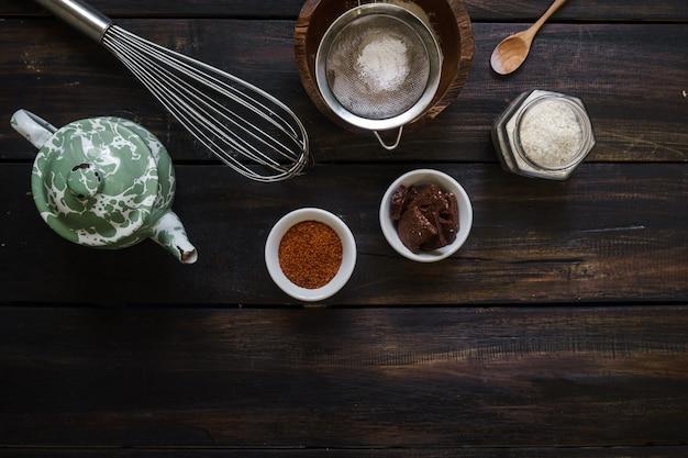 Os utensílios de cozinha são dispostos aleatoriamente em uma mesa de madeira escura.