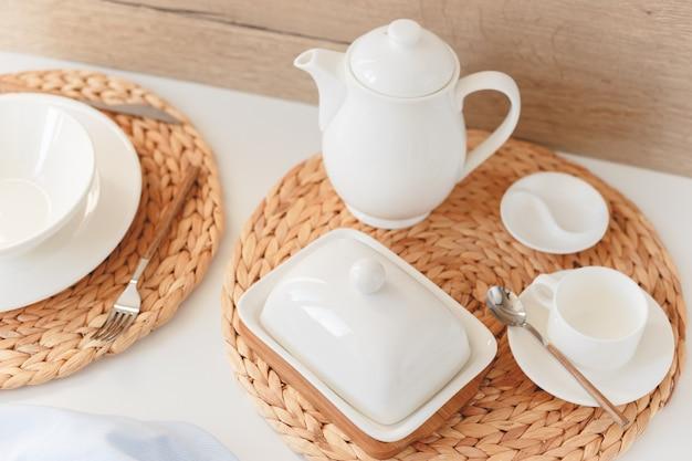 Os utensílios de mesa cerâmicos brancos, o placemat redondo trançado fibra e a cutelaria ajustaram-se no fundo branco. estilo escandinavo.
