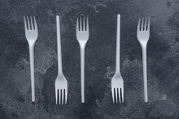 Os utensílios de mesa plásticos descartáveis obstruem na tabela escura com o espaço da cópia.