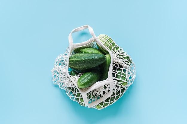 Os vegetais verdes frescos dos pepinos na malha reusável da compra eco-frendly ensacam no fundo azul.