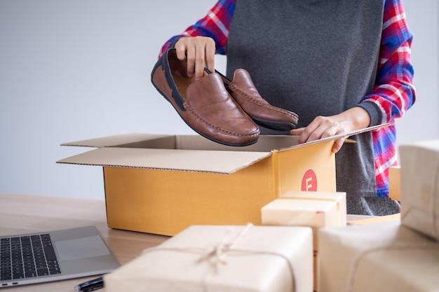 Os vendedores on-line estão colocando os sapatos em uma caixa para entregar produtos aos compradores encomendados no site