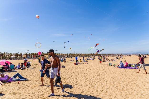 Os veraneantes e os turistas na malvarrosa encalham durante um festival do voo do papagaio livre no verão.
