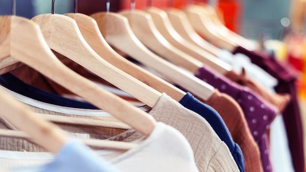 Os vestidos de verão de algodão feitos à mão estão pendurados em um cabide na loja.