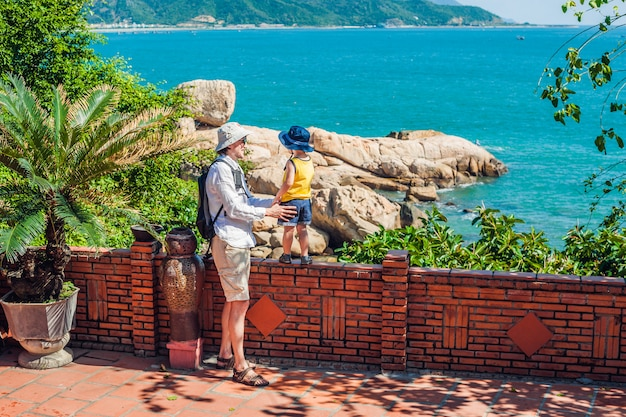 Os viajantes de pai e filho olham para a capa de hon chong, pedra de jardim, destinos turísticos populares em nha trang. vietnã