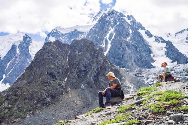 Os viajantes descansam na colina perto da geleira.