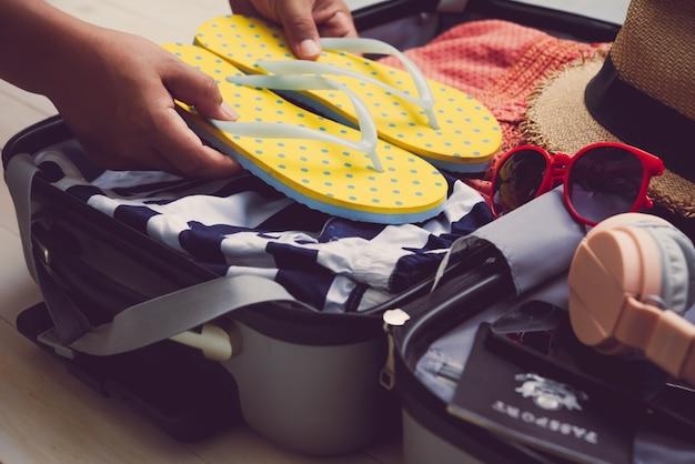 Os viajantes estão empacotando suas malas de viagem, jeans, camisas, passaportes
