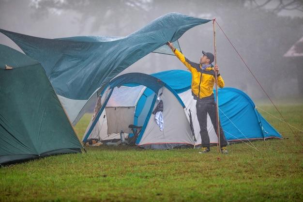 Os viajantes estão reparando tendas durante o chuvoso