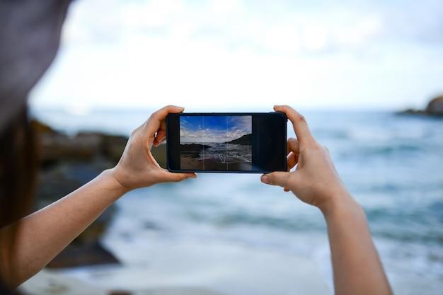 Os viajantes estão tirando foto do mar com um smartphone.