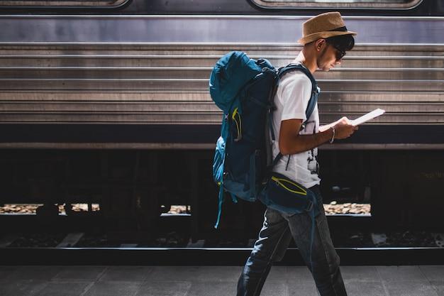 Os viajantes estão viajando de mochila e andando sozinhos na estação de trem.