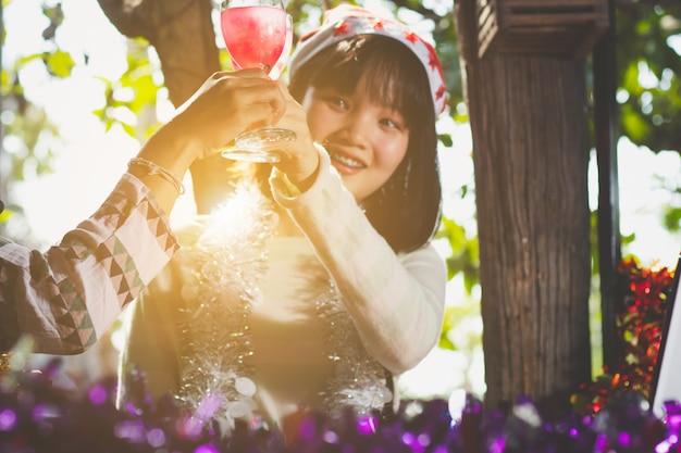Os vidros clinking da menina adolescente de ásia com os amigos no partido do ano novo, sorriem com feliz.
