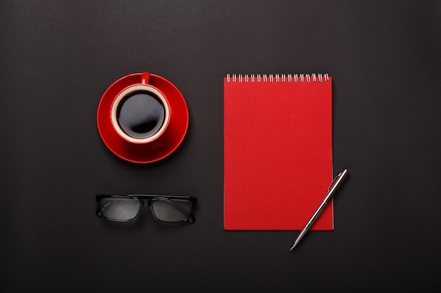 Os vidros vermelhos da pena do bloco de notas do copo de café do fundo preto esvaziam o desktop do lugar.