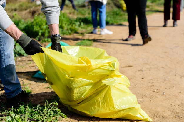 Os voluntários coletam o lixo plástico de um ambiente natural contaminado e o armazenam em sacos.