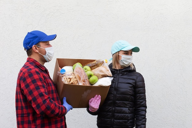 Os voluntários com máscaras protetoras com uma caixa de comida
