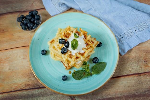 Os waffles belgas clássicos caseiros cozidos frescos cobertos com gelado, mirtilos frescos e hortelã na tabela de madeira, cobrem para baixo a vista. waffles salgados. conceito de pequeno-almoço