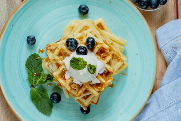 Os waffles belgas clássicos caseiros cozidos frescos cobertos com gelado, mirtilos frescos e hortelã no fundo de madeira, cobrem para baixo a vista. waffles salgados. conceito de pequeno-almoço
