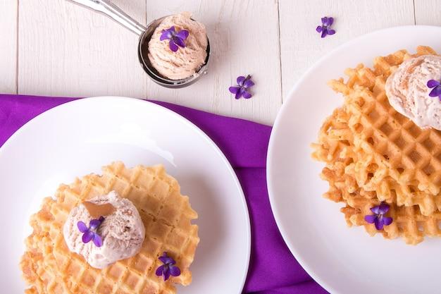 Os waffles belgas com sorvete na placa branca decoravam a flor roxa. vista do topo.