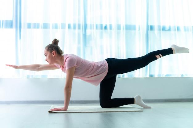 Ostenta a jovem mulher fazendo exercícios de fitness e treino em casa. perder peso e manter a forma. estilo de vida saudável