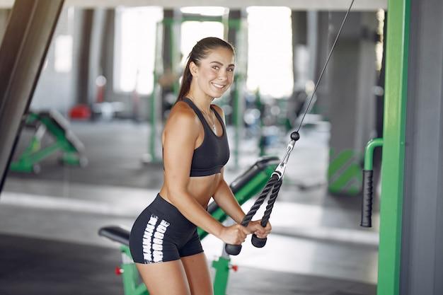 Ostenta a mulher morena em um treinamento de sportswear em uma academia