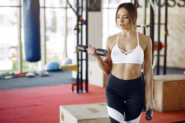 Ostenta a mulher treinando em uma academia de manhã