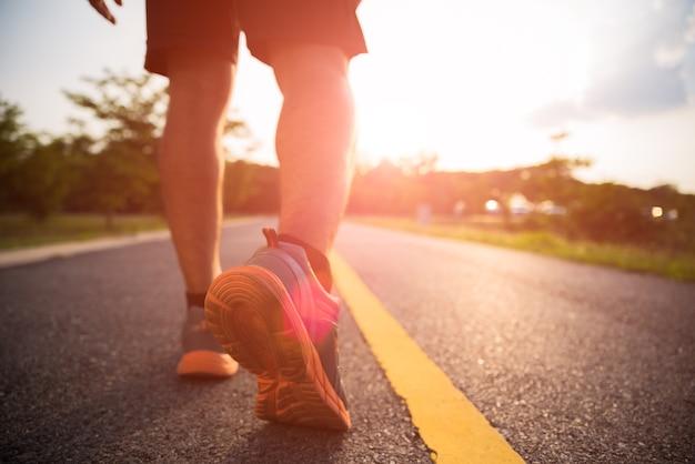 Ostenta as pernas de um homem correndo e andando durante o pôr do sol.