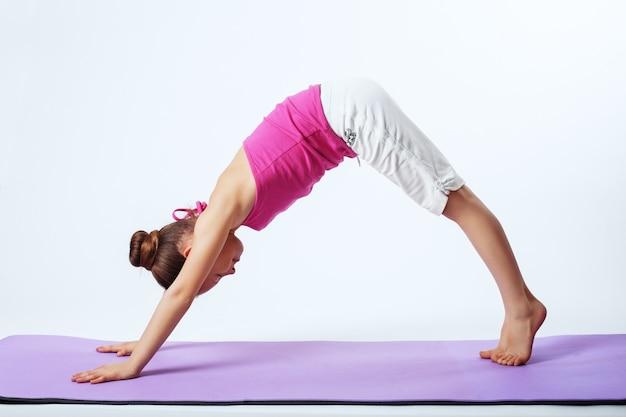 Ostentando uma criança envolvida em exercícios de yoga.