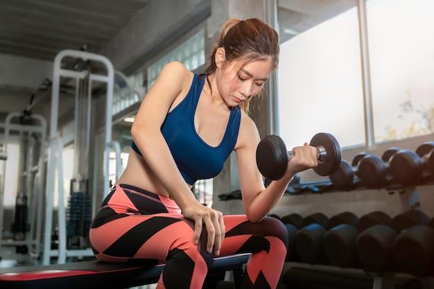 Ostente a mulher asiática no braço de treinamento de sportswear com halteres no ginásio de fitness.
