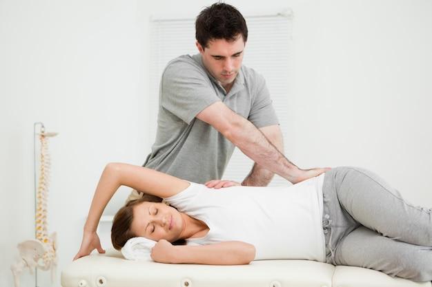 Osteopata cruzando os braços enquanto massageia uma mulher