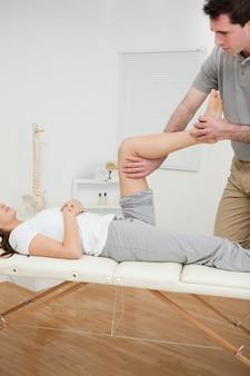 Osteopata grave curvando a perna de uma mulher