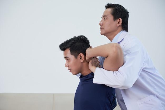 Osteopata trabalhando com um jovem