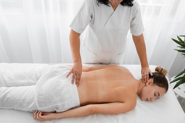 Osteopata tratando uma mulher sem camisa dentro de casa