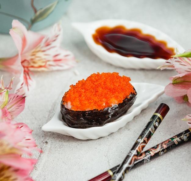 Ostra com caviar vermelho em cima da mesa