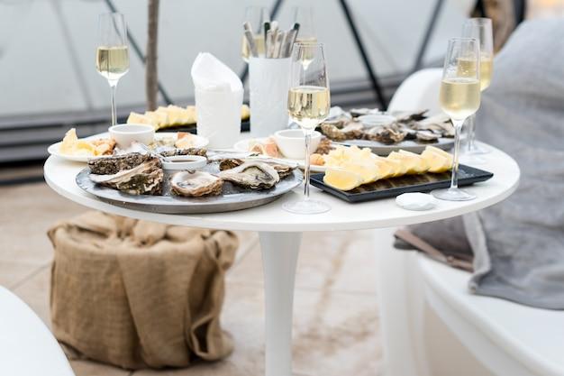 Ostras abertas e limão com vinho branco em cima da mesa.
