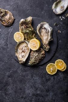 Ostras abertas frescas. frutos do mar saudáveis. jantar no restaurante. comida gourmet. superfície escura