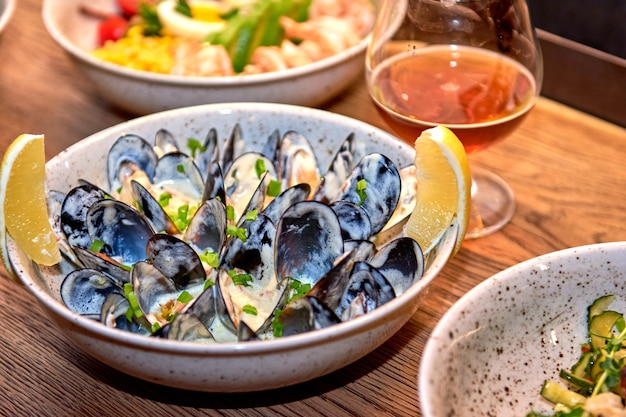 Ostras deliciosas no restaurante sobre uma mesa de madeira, sem pessoas visíveis. saborosos frutos do mar com cerveja no menu do café ou pub.