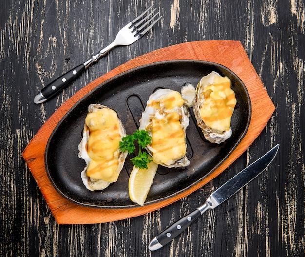 Ostras em uma panela com molho cremoso e queijo