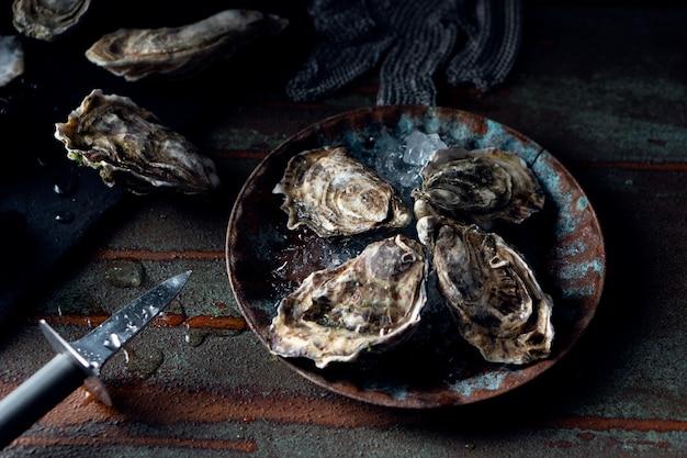 Ostras frescas abertas em um fundo escuro, uma faca e gotas da água. estilo rostik.