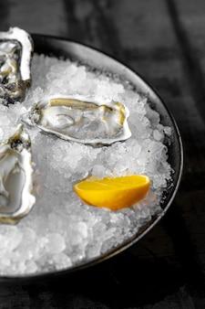 Ostras frescas cruas com gelo e limão em um fundo escuro e rústico