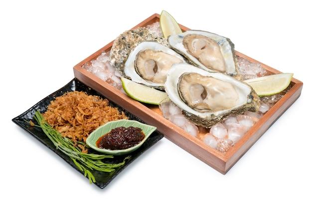 Ostras frescas em um prato de madeira com pasta de pimenta e limão no branco, frutos do mar estilo tailandês