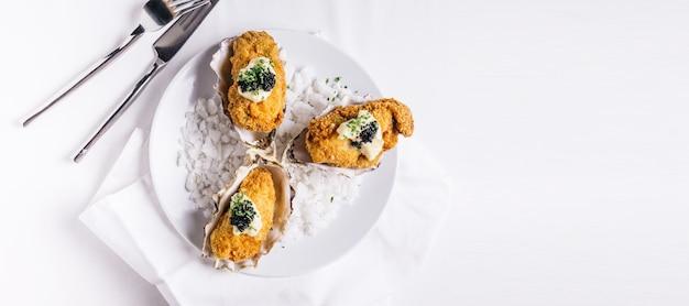 Ostras fritas no topo com maionese e caviar servido em chapa branca com sal marinho