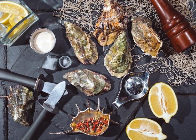 Ostras no prato de pedra com gelo, limão, rede de pesca, pimenta e faca.