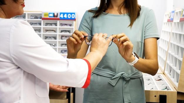 Ótica profissional ajudando cliente a escolher óculos em loja ótica.