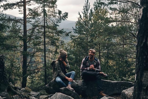 Ótima jornada. lindo casal jovem sentado nas rochas e sorrindo enquanto caminham juntos na floresta