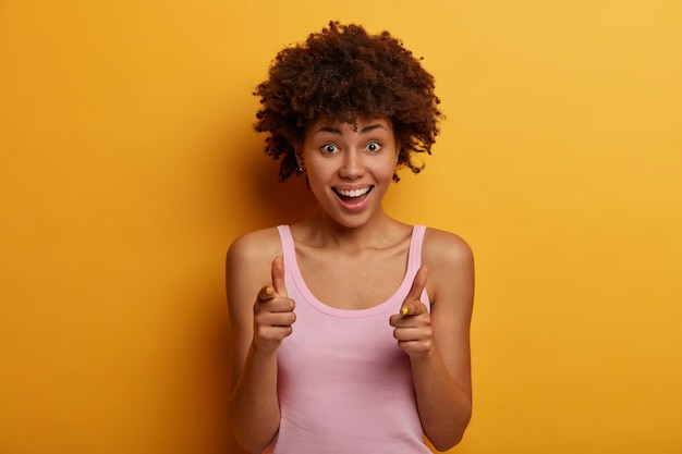 Ótima oferta para você. mulher de cabelo encaracolado alegre mostra sinal de arma, ri positivamente, expressa escolha e escolhe alguém, usa camisa casual, isolada na parede amarela. ei eu lembrei de voce