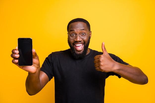 Ótima promoção, escolha! retrato de um homem afro-americano engraçado segurar smartphone mostrar polegar para cima sinal aconselhar selecionar dispositivo sugerir escolher usar camiseta elegante parede amarela isolada