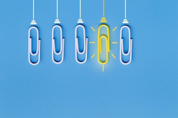Ótimas idéias com clipe de papel, pensamento, criatividade, lâmpada sobre fundo azul, novas idéias